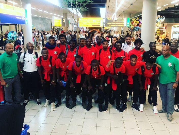 Het Surinaamse voetbalelftal op vliegveld Schiphol. Uiterst links bondscoach Dean Gorré en derde van rechts, in het zwarte T-shirt, Dimitrie Apai (foto Sportmedia Nederland)