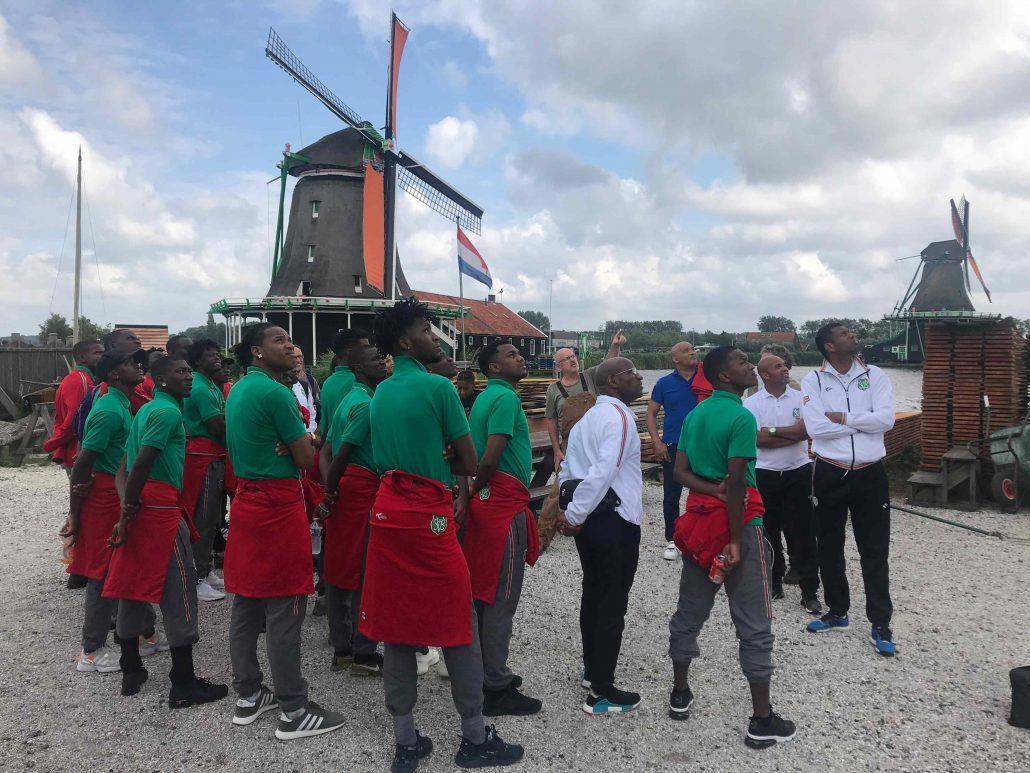 Molenaar Klaas vertelt het Surinaamse elftal over houtzaagmolen 'Het Jonge Schaap'. Middenin de groep, met zwarte Nikes, staat Dimitrie Apai (foto Sportmedia Nederland)
